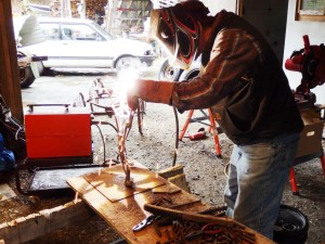 Gene Kennedy welds re-bar into the shape of a dog. (Emily Files)