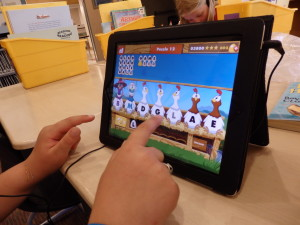 A second grader uses a math learning app on an iPad at Haines School. (Emily Files)