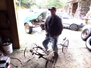 Kennedy demonstrates how he's planning to build onto the antique cart so people will be able to sit on it. (Emily Files)