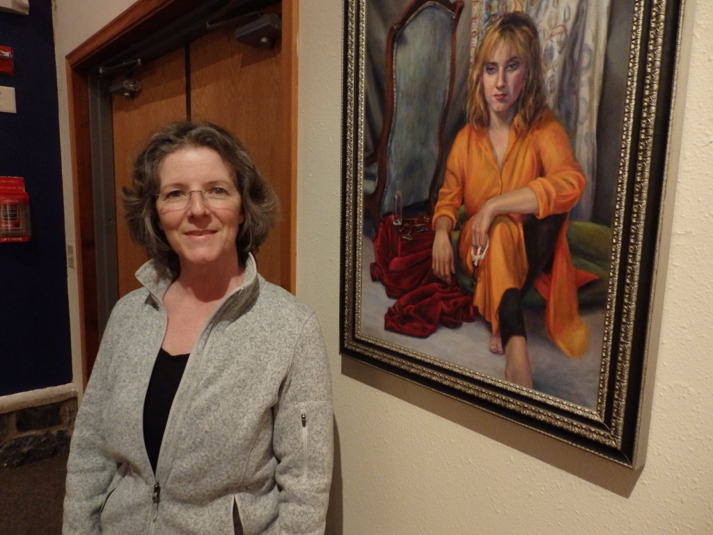 Doreen Dufour with a portrait she painted that's featured in the Sheldon Museum portrait exhibit. (Emily Files)