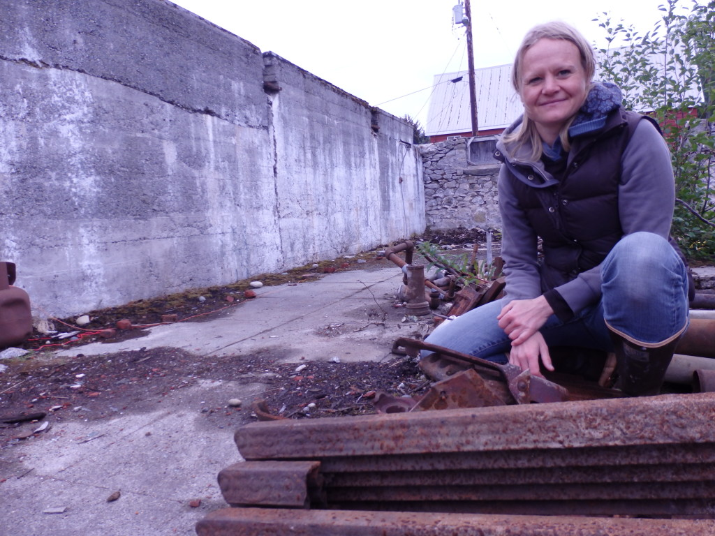 Andrea Nelson is using scrap metal salvaged from the barracks and installing it on the wall to her right. (Emily Files)