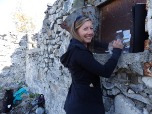 Katie Craney painting on a rusted boiler door on the Fort Seward barracks ruins. (Emily Files)