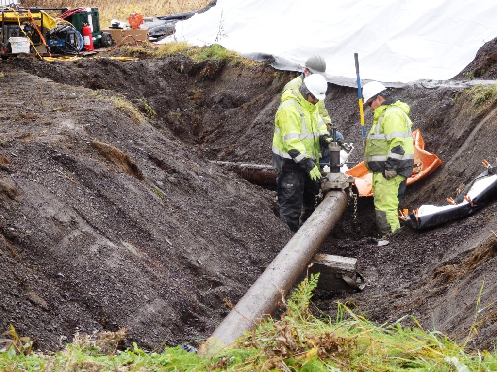 Workers cut a hole in the pipeline to see if there is residual fluid. (Emily Files)