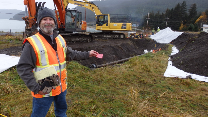 Environmental protection specialist Brian Adams holds a flag that marks one of the soil testing sites. (Emily Files)