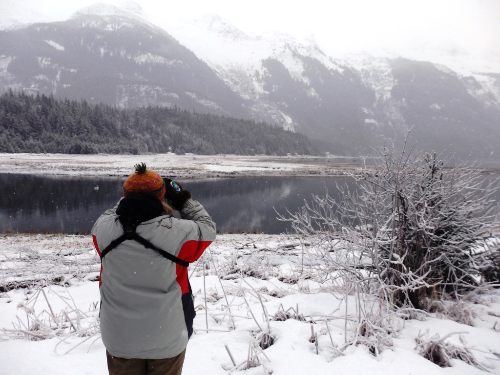 Randles uses binoculars to look for eagles along the Chilkoot River. (Emily Files)