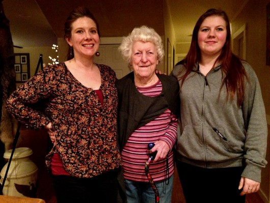 92-year-old Elizabeth Tyner stands at home with granddaughter, Melinda Cook, left, and great-granddaughter, Shawnee Cook, age 18. (Photo by Angela Denning/KFSK)