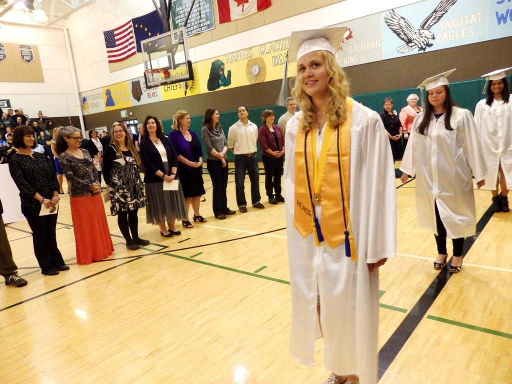 Valedictorian Kayley Swinton. Teachers stand to the right of graduates. (Emily Files)