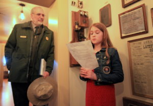 Dr. Herbert Frost, National Park Service Director for Alaska listens as fourth-grader Abigail Tranel talks about one of Skagway's first telephones. (NPS photo)