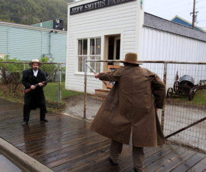 Jon Baldwin portrays Soapy Smith as he confronts Frank Reid, played by Jeff Brady, in a reenactment of the infamous shootout. (NPS photo)