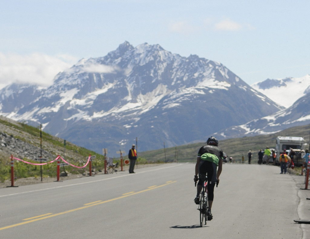 A solo rider crests the summit during the 2016 Kluane-Chilkat International Bike Relay. (Jillian Rogers)