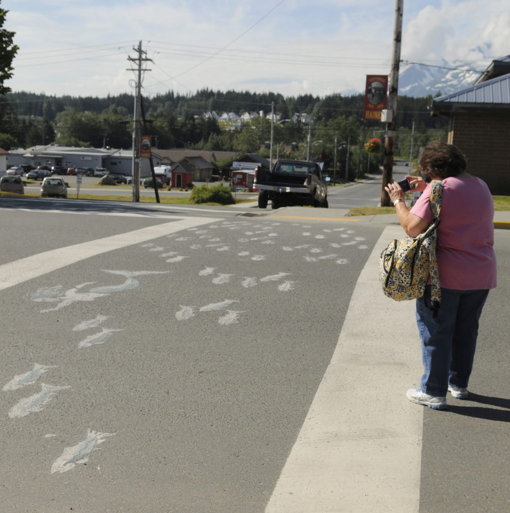 A tourist snaps a photo of the salmon mural on Main Street on Wednesday. The Alaska Department of Transportation told the borough to remove the art as it poses a safety risk on the state road. (Jillian Rogers)