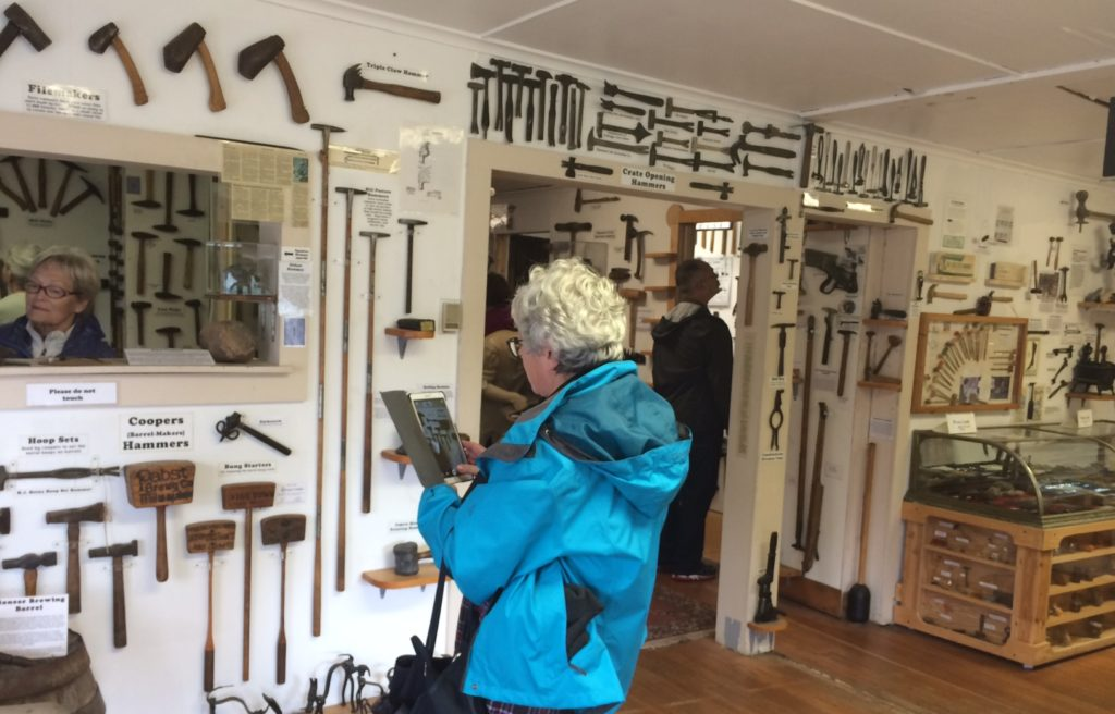 A cruise ship guest snaps photos of the extensive hammer collection at the Hammer Museum in Haines on Wednesday, Aug. 10, 2016. Wednesdays are the museum's busiest day. (Photo by Jillian Rogers, KHNS – Haines)