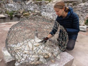 Sarah Bishop finishes up her installation by placing glass fish in a copper wire nest. (Emily Files)