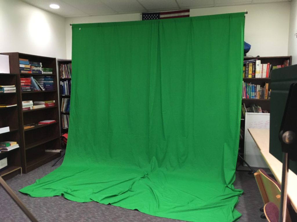 Students use a green screen to record videos in the library. (Abbey Collins)