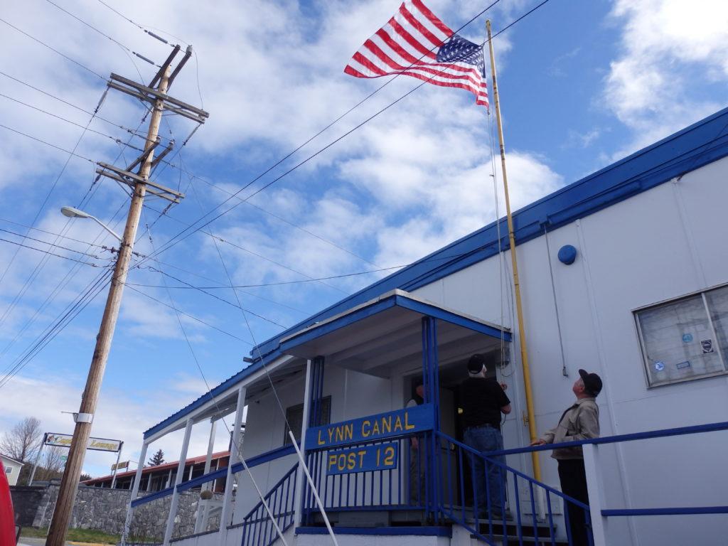 Legion members raise the flag outside of Lynn Canal Post #12. (Emily Files)