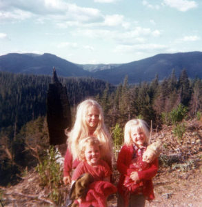 Plachta (holding doll) with her brother and sister on the edge of a clearcut. (Courtesy Jessica Plachta)