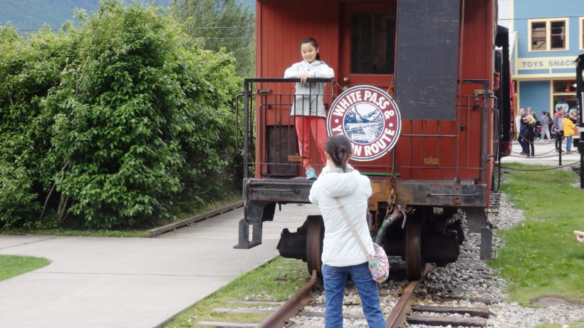 Tourists take pictures with a White Pass and Yukon Route Railroad train car. (Emily Files)