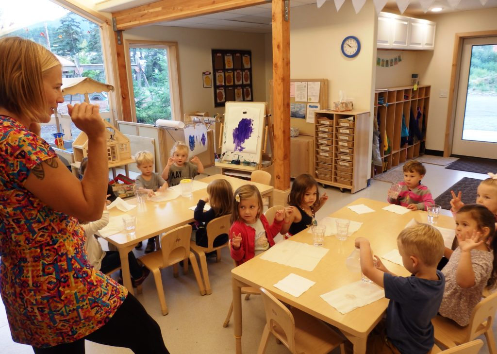 Teacher Alissa Henry leads preschoolers in an activity before snack time during the first week of school. (Emily Files)