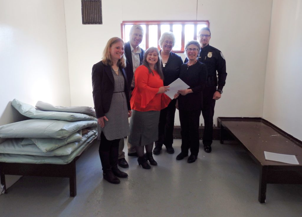 DOC Commissioner Dean Williams, Pretrial Director Geri Fox, Haines Mayor Jan Hill, Haines Borough Manager Debra Schnabel and Haines Police Chief Heath Scott pose in a Haines jail cell with a revised community jails contract. (Emily Files)