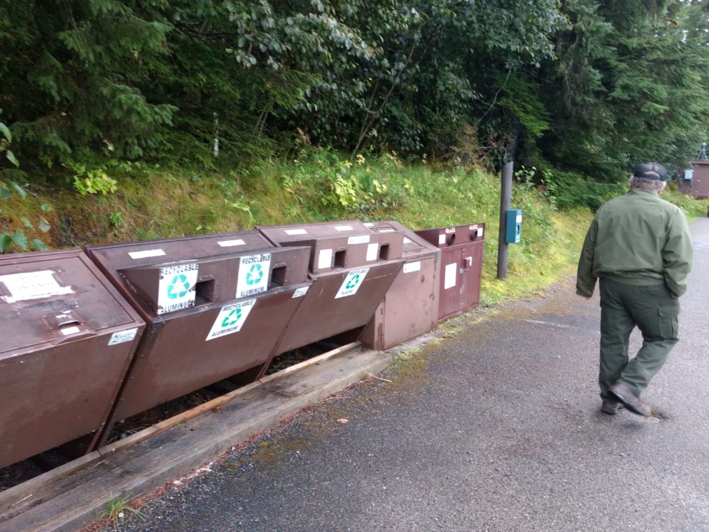 Mark Ortega, utilities supervisor at Glacier Bay National Park, walks past a row of recycling bins on Sept. 5 near the National Park Service's visitors center at Bartlett Cover (Jacob Resneck)