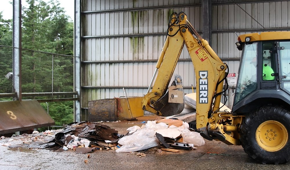 Jim Walters, with Waste Connections, operates a front-end loader to push trash aboard a container van, staged on the lower level of the Sitka Waste Transfer Station. The containers are barged to Seattle. (Robert Woolsey/KCAW)
